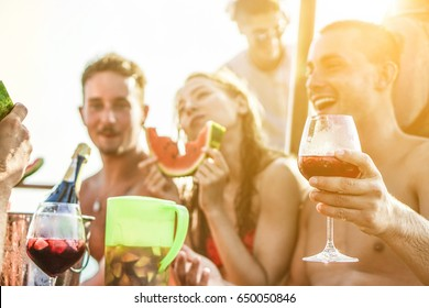 Happy friends drinking sangria wine and eating watermelon at boat party - Young people having fun in summer vacation - Exclusive vacation , friendship , travel concept - Focus on right man hand glass