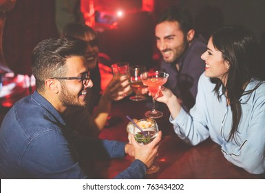 Happy friends drinking and toasting cocktails in a jazz bar - Young people cheering and laughing together in a club at night - Friendship, lifestyle, nightlife concept