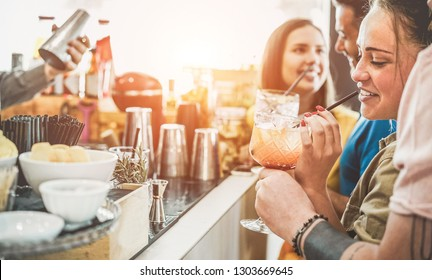 Happy friends drinking in vintage cocktails bar outdoor - Young people having party at sunset in exclusive club - Youth, friendship and fun concept concept - Focus on right woman face