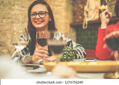 Happy friends drinking wine inside vintage trendy bar - Fashion people having fun at appetizer evening - Youth, friendship, party and trends concept - Focus on woman face