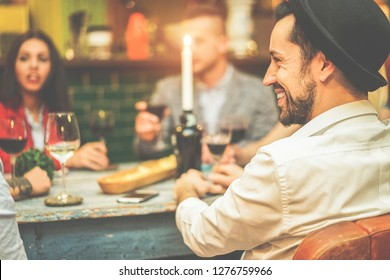 Happy friends drinking wine inside vintage trendy bar - Fashion people having fun at appetizer evening - Youth, friendship, party and trends concept - Focus on right man face
