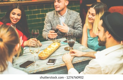 Happy friends drinking wine inside vintage trendy bar - Fashion people having fun at appetizer evening - Youth, friendship, party and trends concept - Focus on right bottom hand