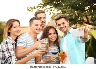 Happy friends with drinks taking selfie outdoors
