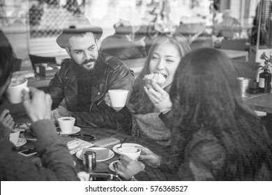 Happy friends eating breakfast and drinking coffee with milk in bar cafeteria - View through glass with reflection - Black and white editing - Focus on bearded man - Warm filter