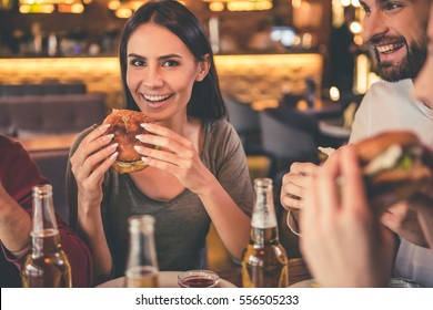 Happy friends are eating burgers and smiling while spending time together in cafe