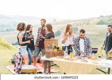 Happy friends eating at picnic lunch in italian vineyard outdoor - Young people having fun on gastronomic weekend tuscany tour - Friendship, summer and food concept - Main focus on center man face