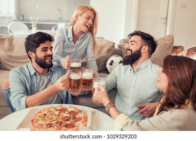 Happy friends eating pizza and watching tv at home.People,food,fun and happiness concept.
