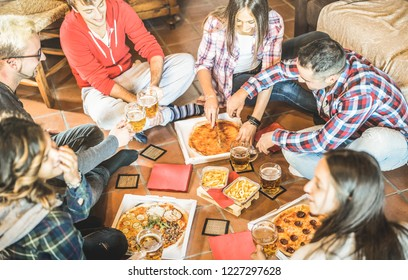 Happy friends eating take away pizza at home after work - Friendship concept with young people enjoying time together and having genuine fun in start up office - Focus on beers and french fries