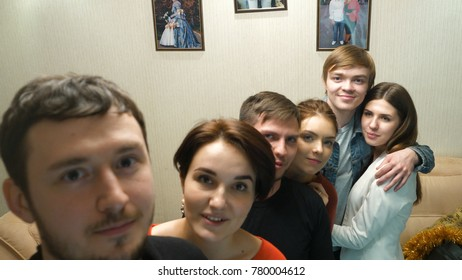 Happy friends enjoying time together and making a selfie. Group of young friends taking selfie in home interior. Handsome guy is making selfie with his friends at the party on his phones camera