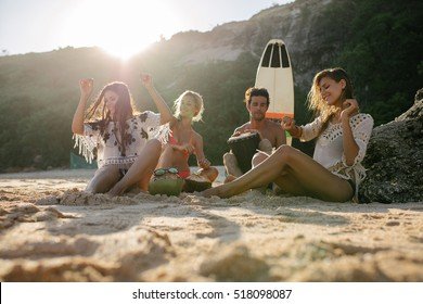 Happy friends enjoying vacation on the beach. Happy young people having fun at beach party, women dancing and man playing dumbek.