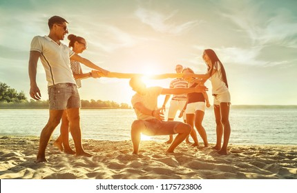 Happy Friends funny game on the beach under sunset sunlight in summer sunny day.