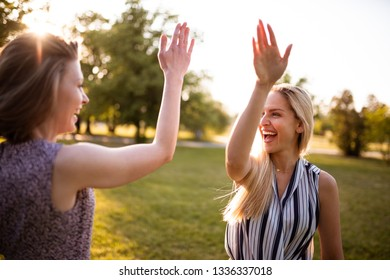 Happy friends giving high five to each other
