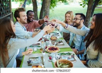 Happy friends with glasses of red wine toasting by festive table