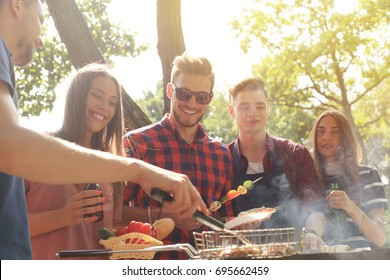 Happy friends grilling meat and enjoying barbecue party outdoors.