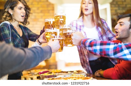 Happy friends group drinking beer and eating pizza at bar restaurant - Friendship concept with young people having fun together at risto pub pizzeria - Focus on middle pint glass - Vivid warm filter