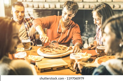 Happy friends group eating pizza at chalet bar restaurant - Friendship concept with young people enjoying time together and having genuine fun at rustic pizzeria  - Focus on guy cutting slices
