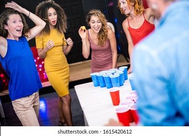 Happy friends group playing beer pong in youth hostel - Travel and fun concept with backpackers having genuine fun together at guesthouse gameroom - Vivid color filter with focus girl throwing ball