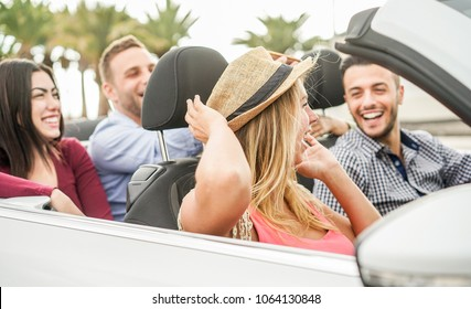 Happy friends with hands up having fun in convertible car on summer vacation - Young people laughing and smiling together during travel holidays - Youth lifestyle concept - Focus on hat