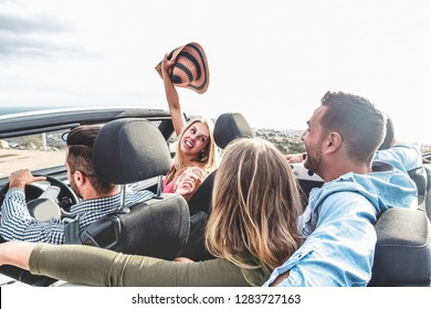 Happy friends with hands up having fun in convertible car on summer vacation - Young people laughing and smiling together during travel holidays - Youth lifestyle concept - Focus on right man head