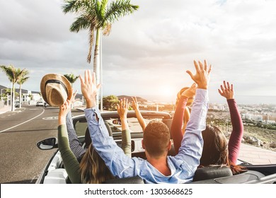 Happy friends with hands up having fun in convertible rented car on summer vacation - Young people enjoyng travel holidays - Youth lifestyle concept - Focus on guys heads