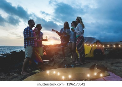 Happy friends having barbecue party party next to the ocean at evening - Young millennials friends drinking beer and playing music at night picnic - Nightlife and fun concept - Focus on left guy face