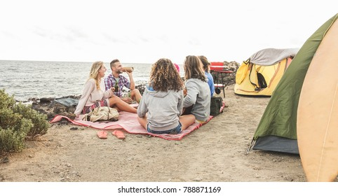 Happy friends having barbecue picnic next to the ocean - Trendy people having fun playing music, camping and laughing together in holidays - Travel, vacation, party and friendship concept