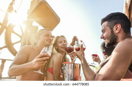 Happy friends having boat party outdoor with sangria and champagne  - Young people toasting wine in exclusive rich summer vacation  around europe - Travel ,friendship concept - Main focus on right man