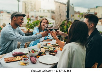 Happy friends having dinner party outside sitting in cozy restaurant terrace with a garden celebrating a long-awaited meeting or birthday making toasts with red wine, laughing and having fun together
