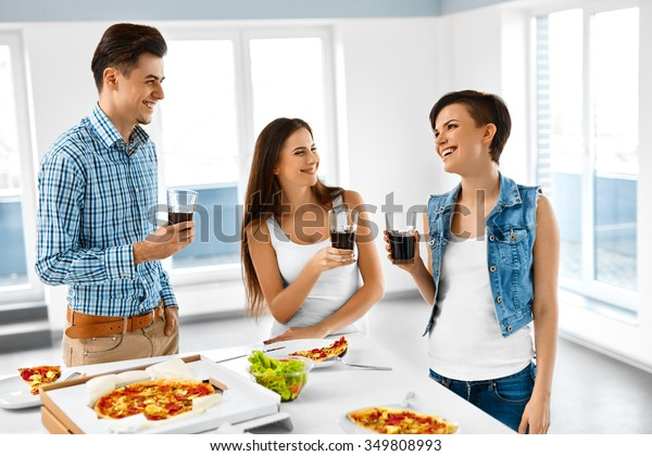 Happy Friends Having Dinner Party At Home. Smiling People Eating Pizza, Drinking Soda And Having Fun Together Indoors. Fast Food, Friendship, Leisure Concept. Celebration. Cheers