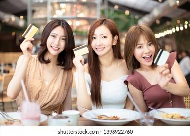 Bonnes amies dînant et montrant une carte de crédit au restaurant