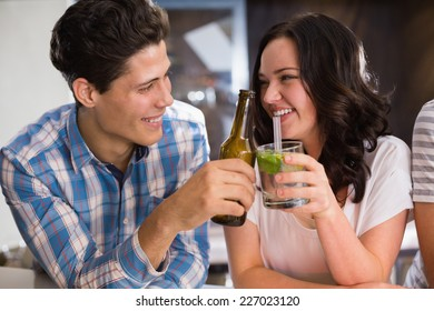 Happy friends having a drink together at the bar