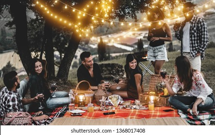 Happy friends having fun at bbq dinner with vintage lights outdoor drinking wine - Young people celebrating on weekend summer night - Friendship, party and youth concept - Focus on center couple