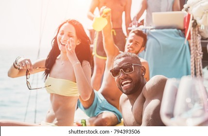 Happy friends having fun at boat party - Young people laughing and drinking in exclusive tropical sea tour - Youth lifestyle, travel and summer vacation concept - Soft focus on black man