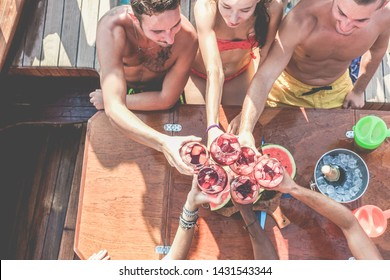 Happy friends having fun cheering with wine in boat party - Young people enjoying summer vacation together toasting sangria and eating watermelon - Youth and friendship concept - Soft focus on glasses