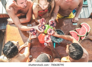Happy friends having fun cheering with wine in boat party - Young people enjoying summer vacation together toasting sangria an eating watermelon - Youth and friendship concept - Focus on glasses