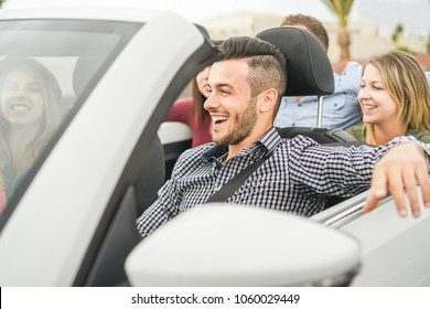 Happy friends having fun in convertible car on summer vacation - Young people laughing and smiling during summer vacation - Focus on man face - Travel, rich lifestyle and youth concept