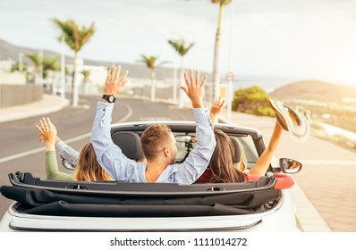 Happy friends having fun in convertible car at sunset in vacation - Young people making party and dancing in a cabrio auto during their road trip - Friendship, travel, youth lifestyle concept