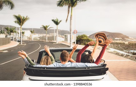 Happy friends having fun in convertible car on vacation - Young millennial people driving on cabriolet in summer holidays - Transport and youth lifestyle concept