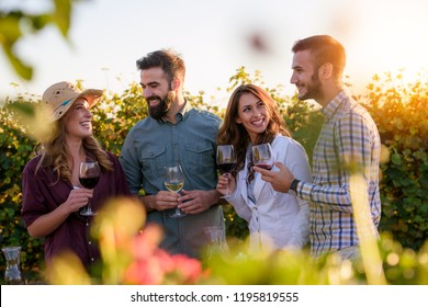 Happy friends having fun drinking wine at winery vineyard - Friendship concept with young people enjoying harvest time together