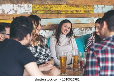 Happy friends having fun drinking beer at rustic bar - Friendship concept with young people enjoying time together at rustic pub drinking beer