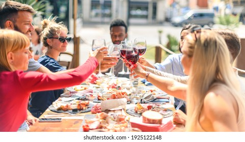 Happy friends having fun drinking red wine at restaurant wearing face masks - Young people eating brunch at bar together - New normal lifestyle concept about dining - Focus on glasses