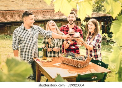 Happy friends having fun drinking wine at winery vineyard - Friendship concept with young people enjoying harvest together at farmhouse - Warm desaturated filter with contrast tone - Leaves in frame
