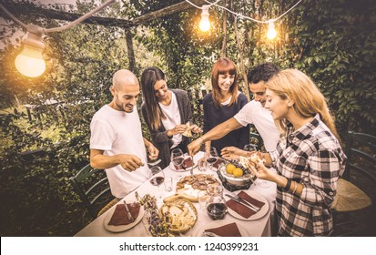 Happy friends having fun eating local food at garden fest - Friendship and holidays concept with people together at farmhouse vineyard winery - Warm vintage filter with artificial electric lighting