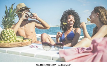 Happy friends having fun and eating fresh pineapple fruit at boat party - Young people taking photos in caribbean sea tour - Youth, tropical, travel and summer vacation concept - Focus on black girl