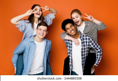 Happy friends having fun. Guys giving piggyback ride to girls, fooling over orange background
