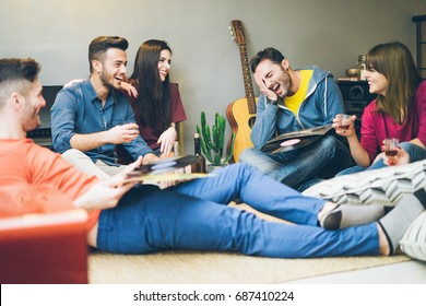 Happy friends having fun in home living room drinking and laughing  - Young students enjoying time together listening music with vinyl records - Main focus on right man - Vintage retro camera filter