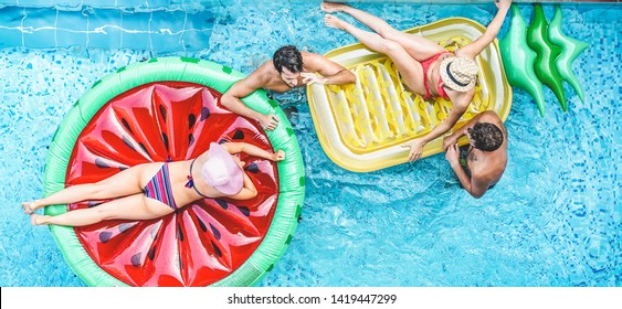 Happy friends having fun inside swimming pool - Young people talking and laughing on summer holidays vacation - Travel, holidays, youth lifestyle, friendship and tropical concept