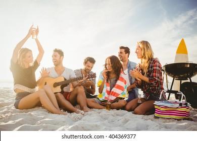 Happy friends having fun near barbecue on the beach