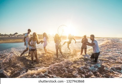 Happy friends having fun on the beach at sunset - Young people playing inside sea water outdoor in summer vacation at gold hour - Friendship, youth,travel concept - Soft focus on right guys