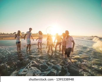 Happy friends having fun on the beach at sunset - Young people playing inside sea water outdoor in summer vacation - Friendship, youth, travel concept - Soft focus on right guys